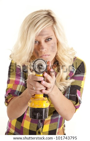 A woman is holding a yellow drill and pointing it with a mean expression on her face. - stock photo