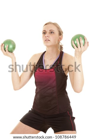 A woman is holding two medicine balls and working out. - stock photo