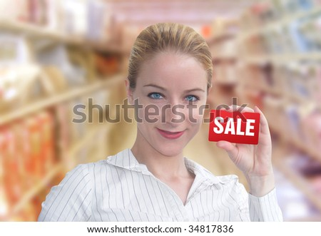 A woman is holding up a red card that has the word SALE on it. She looks happy and is standing in a department store. - stock photo