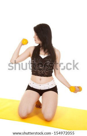 A woman is holding weights and kneeling down while curling them to the side. - stock photo