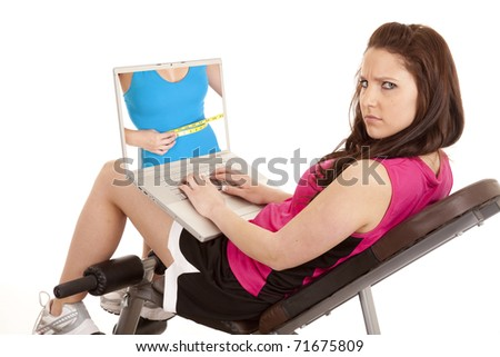 A woman is in fitness attire holding a laptop and scowling at the fit woman on the screen. - stock photo