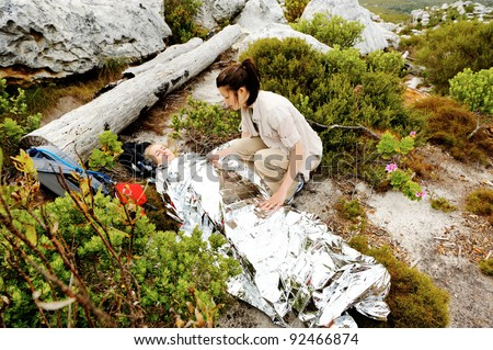A woman is injured while hiking outdoors. her friend has covered her with and emergency blanket and checks on her using a first aid kit - stock photo