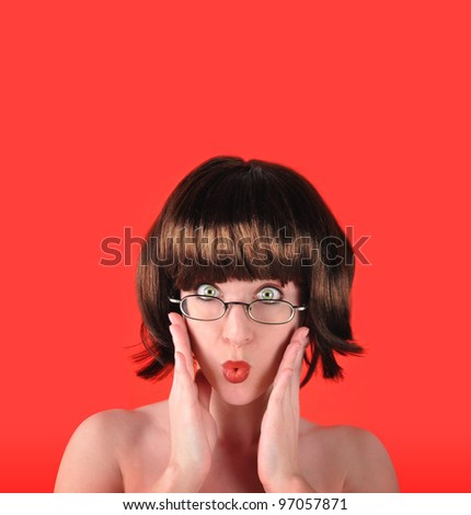 A woman is isolated on a red background with brown hair and glasses and looks surprised or worried. Add your text to the copyspace above. - stock photo