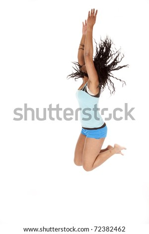 A woman is jumping.  Side view with legs up. - stock photo
