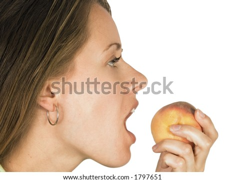 A woman is just about to eat some fruit
