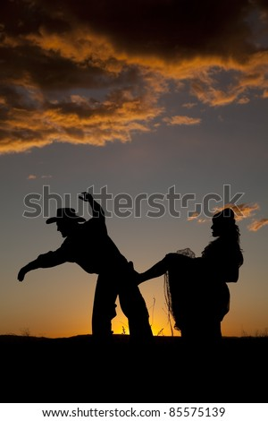 A woman is kicking a cowboy in the butt in the sunset. - stock photo
