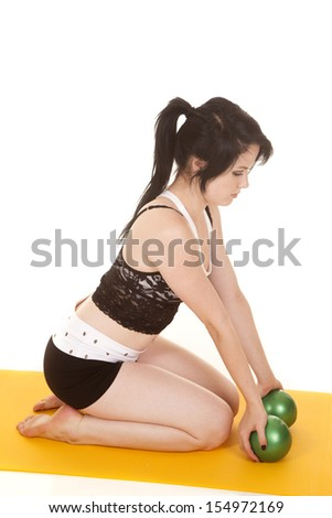 A woman is kneeling on a yellow mat with balls. - stock photo