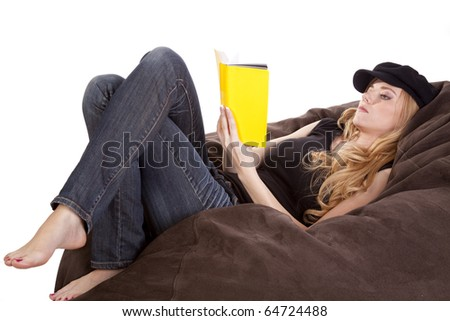 A woman is laying on a bean bag and reading.