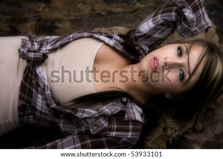 A woman is laying on her back on a rock looking up. - stock photo
