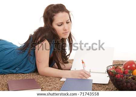A woman is laying on the floor doing homework.