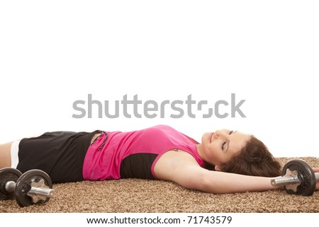 A woman is laying on the floor with weights exhausted. - stock photo
