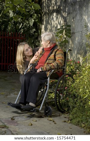 A woman is leaning down next to an elderly woman in a wheelchair.  The younger woman has her arms on the elderly woman, and they are looking and smiling a each other.  Vertically framed shot. - stock photo