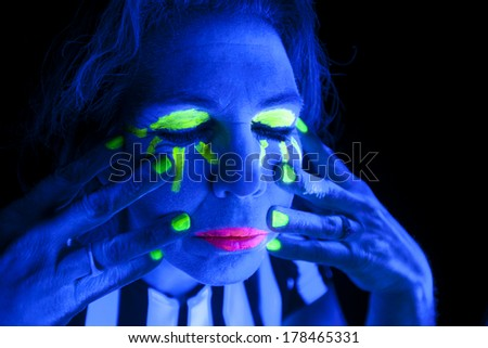 A woman is lit up with a black light and has her eyes closed.