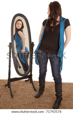 A woman is looking at her butt in a mirror.