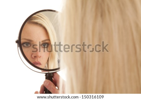 A woman is looking into a mirror up close