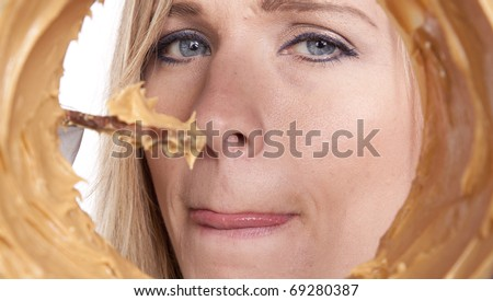 A woman is looking into a peanut butter jar. - stock photo