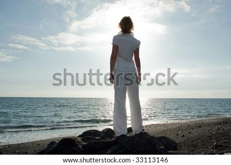 A woman is looking over the sea to the horizon. - stock photo