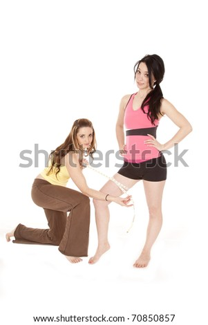 A woman is measuring another womans thigh.