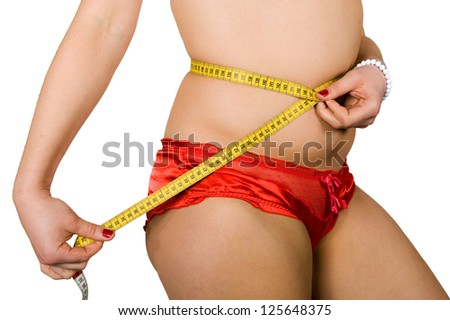 A woman is measuring her size around her waist with a tape-measure
