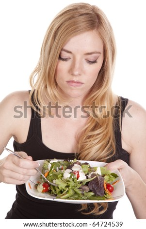 A woman is not happy about eating a salad. - stock photo