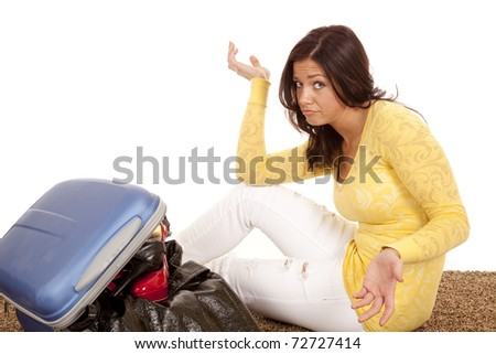 A woman is not sure how to make things fit in her suitcase - stock photo