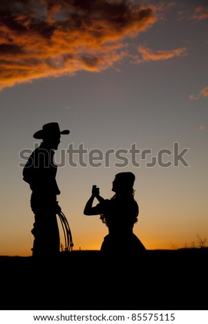 A woman is on her knees pleading with her cowboy in the sunset.