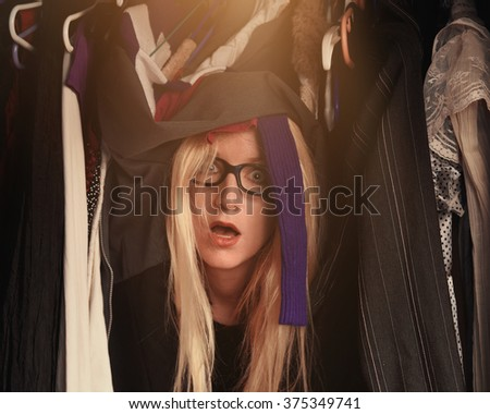 A woman is overwhelmed in a closet of messy clothes with glasses for a style or fashion concept. - stock photo