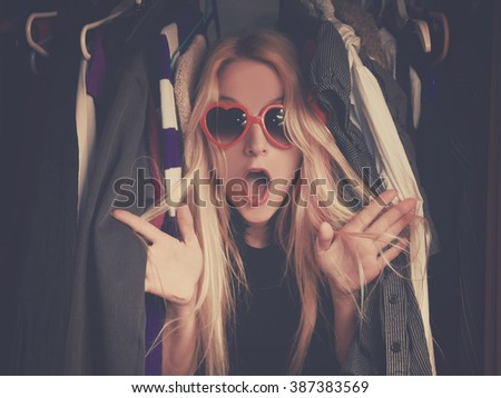 A woman is overwhelmed in a closet of messy clothes with red glasses for a style or fashion concept. - stock photo