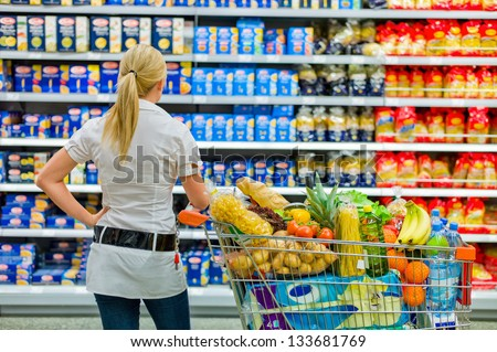 a woman is overwhelmed with the wide range in the supermarket when shopping. - stock photo