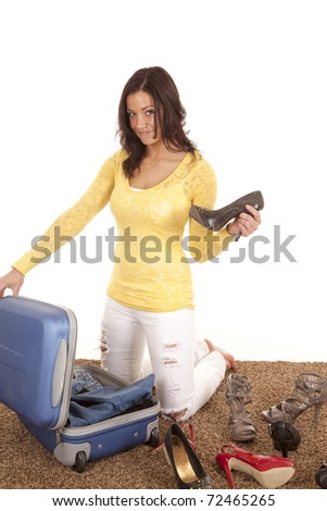 A woman is packing her suitcase putting in a shoe. - stock photo