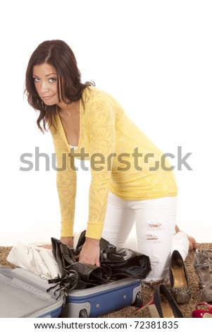 A woman is packing her suitcase trying to get everything to fit. - stock photo