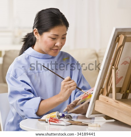 A woman is painting a picture on an easel.  She is looking away from the camera.  Square framed shot. - stock photo