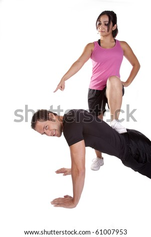A woman is pointing and making the man do pushups. - stock photo