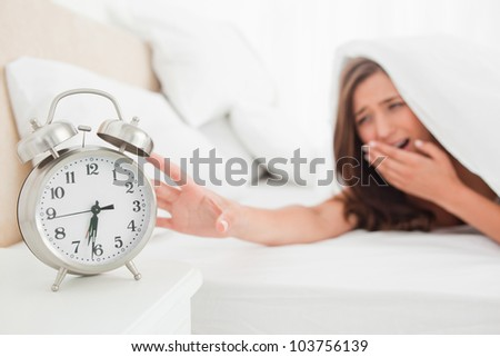 A woman is reaching out to silence her alarm clock while underneath her blanket in bed.