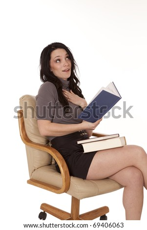A woman is reading a book and holding her heart.