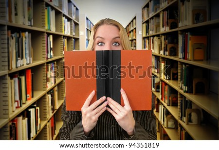 A woman is reading a book in the library and looks surprised. Use it for an education or academic concept.