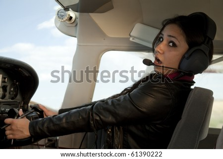 A woman is scare and flying a plane. - stock photo