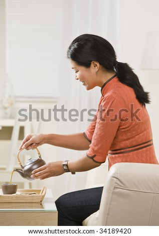 A woman is seated on the living room sofa and pouring herself a cup of tea from the kettle.  She is looking away from the camera.  Vertically framed shot. - stock photo