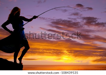 A woman is silhouetted in the sunset with a fishing pole bent to the water. - stock photo