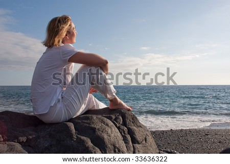 A woman is siting and relaxing on a beach. - stock photo
