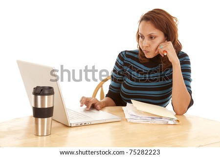 A woman is sitting at a table with a laptop working.