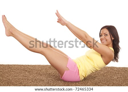 A woman is sitting in a crunch position with a smile - stock photo
