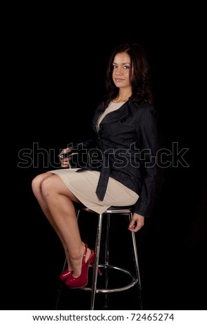 A woman is sitting in a stool with red shoes on. - stock photo