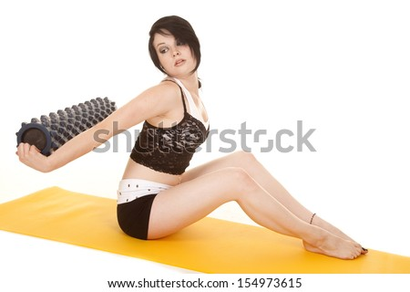 A woman is sitting on a mat holding a roll behind her back. - stock photo