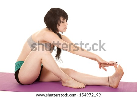 A woman is sitting on a mat stretching her leg. - stock photo