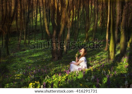 A woman is sitting on a meadow with flowers and enjoying the beauty of nature - stock photo