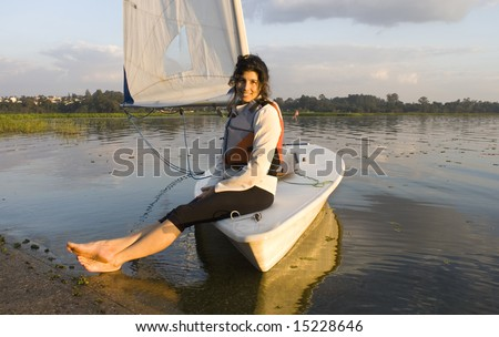 A woman is sitting on a sailboat.  She is smiling and looking at the camera.  Horizontally framed shot. - stock photo