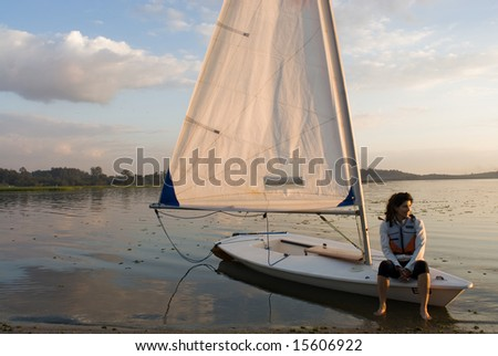 A woman is sitting on a sailboat.  She is smiling and looking away from the camera.  Horizontally framed shot. - stock photo