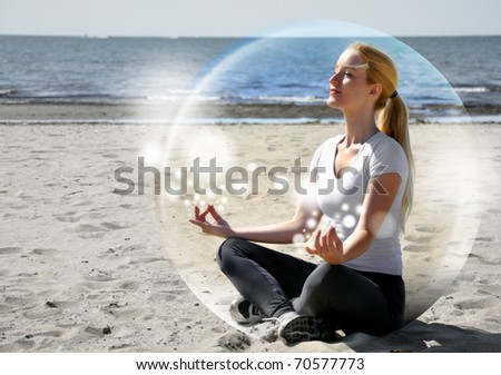 A woman is sitting on the beach inside a bubble with peace and tranquility. She is meditating and there are sparkles. - stock photo