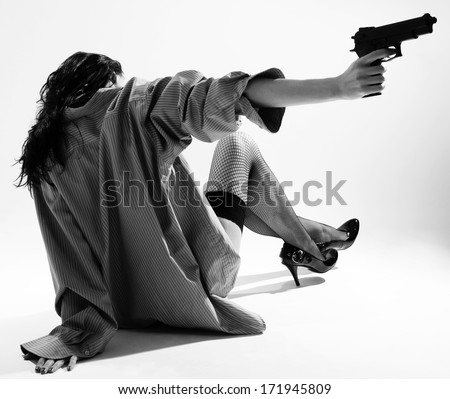 A woman is sitting on the floor and shooting with a gun without aiming. She is wearing a male shirt, fishnet stockings. This is a black-and-white photo with personal perspective. - stock photo